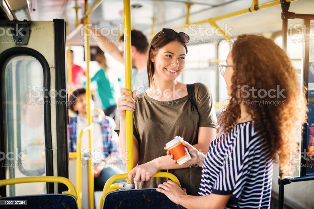 Two beautiful best friends are talking while standing in a bus full of people. stock photo
