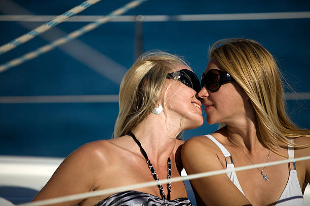 Two beautiful blonde women Two beautiful blonde women posing on a boat middle aged women in bikinis stock pictures, royalty-free photos & images