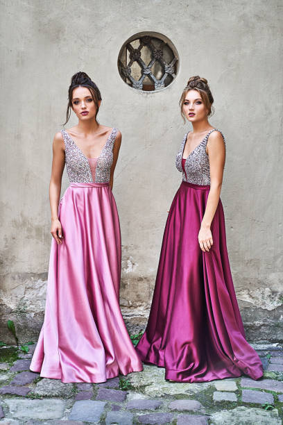 Two beautiful bridesmaids girls blonde and brunette ladies wearing elegant full length purple violet lilac lavender satin folded bridesmaid dress with silver sequined camisole top with sequins. European old town location for wedding day. stock photo