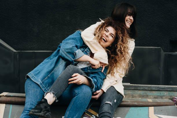Dos hermosas chicas caucásicas divertirse riendo abrazando. - foto de stock