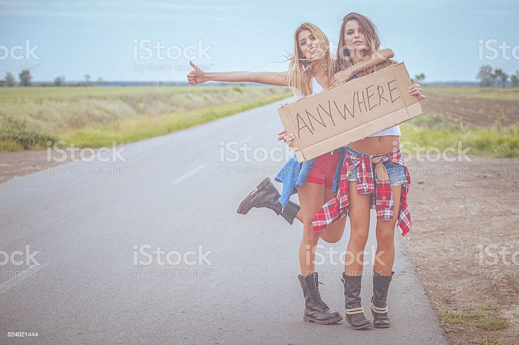 Two beautiful cheerful hipster friends hitchhiking by the road stock photo