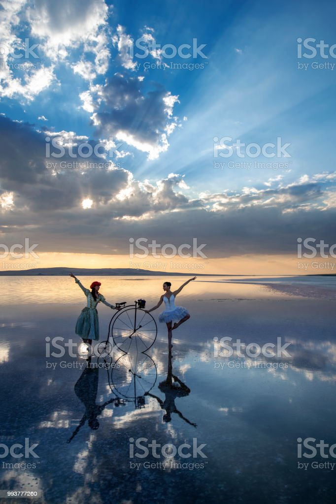 Two beautiful dancers on the lake at sunset. stock photo