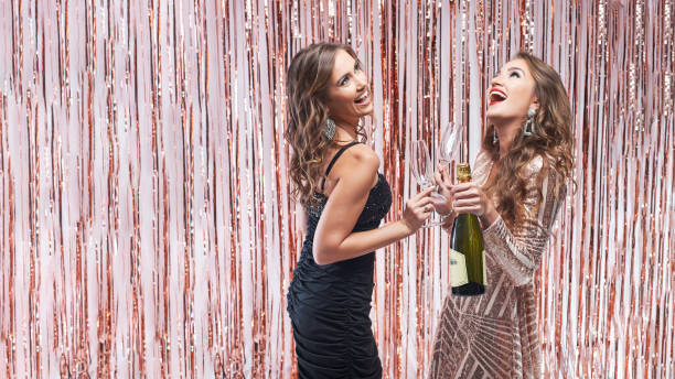 Two beautiful elegant women drinking champagne against sparkling decoration background. stock photo