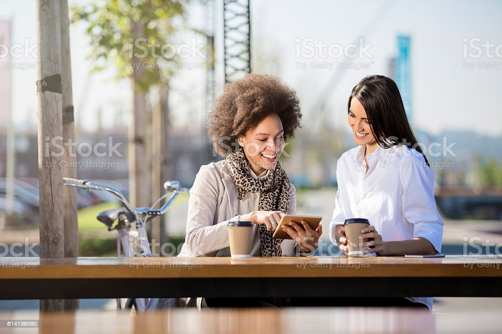 Two beautiful females drinking coffee to go stock photo