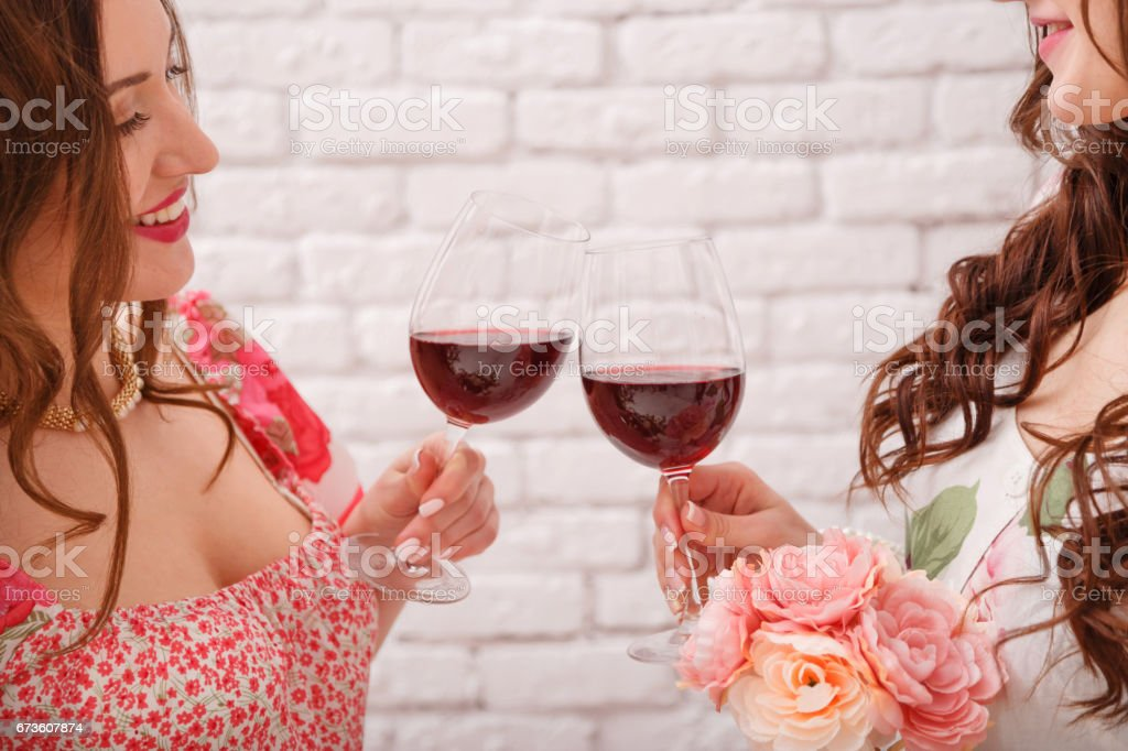 Two beautiful girlfriends are drinking red wine. Glasses close-up. stock photo