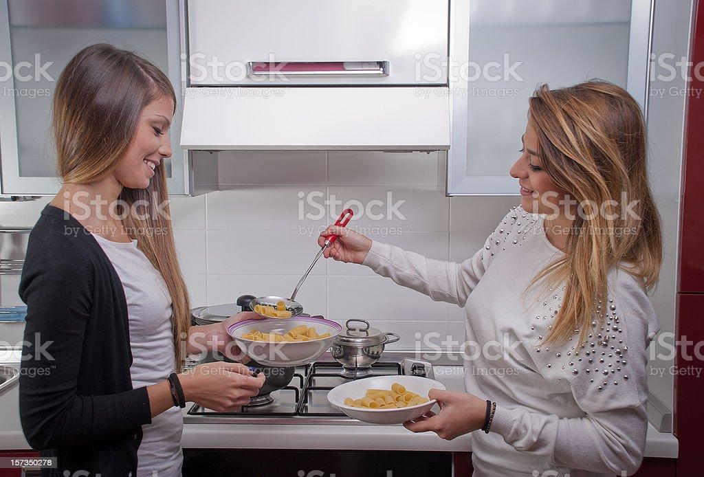 Zwei wunderschöne Mädchen Kochen Nudeln in modernen Küche – Foto