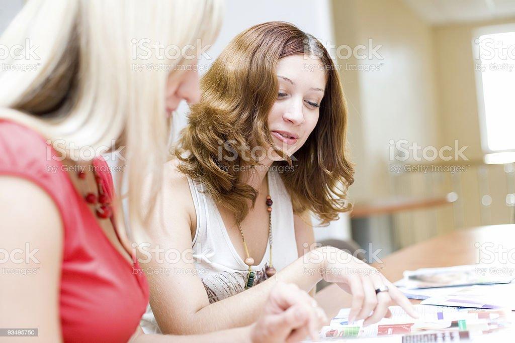 Two beautiful girls discuss the fashion magazine stock photo