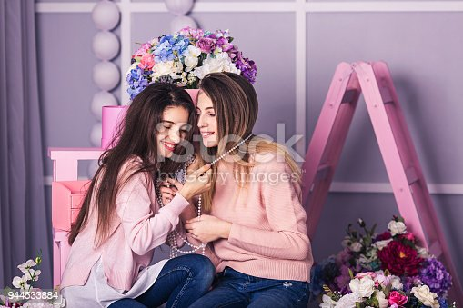 istock Two beautiful girls in jeans and pink sweater are smiling at background of floral decorations in studio. 944533884