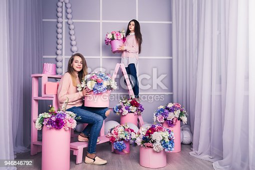 961500822 istock photo Two beautiful girls in jeans and pink sweater in studio with decor of flowers in baskets. 946846792