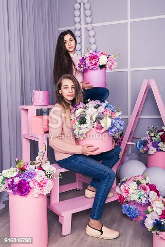 961500822 istock photo Two beautiful girls in jeans and pink sweater in studio with decor of flowers in baskets. 946846798