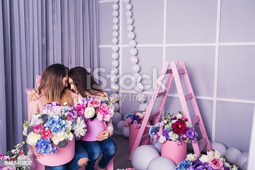 961500822 istock photo Two beautiful girls in jeans and pink sweater in studio with decor of flowers in baskets. 946846802