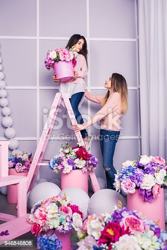 961500822 istock photo Two beautiful girls in jeans and pink sweater in studio with decor of flowers in baskets. 946846808