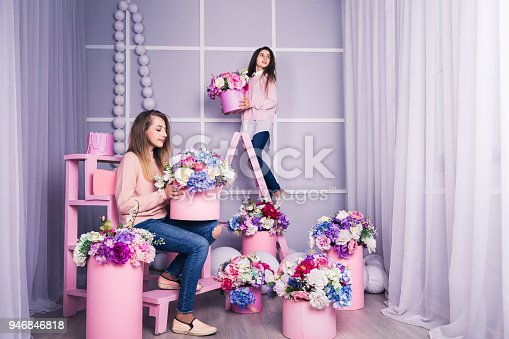 961500822 istock photo Two beautiful girls in jeans and pink sweater in studio with decor of flowers in baskets. 946846818