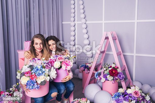 961500822 istock photo Two beautiful girls in jeans and pink sweater in studio with decor of flowers in baskets. 946846826
