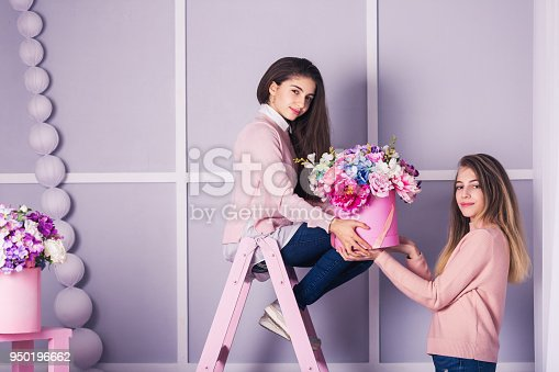 961500822 istock photo Two beautiful girls in jeans and pink sweater in studio with decor of flowers in baskets. 950196662