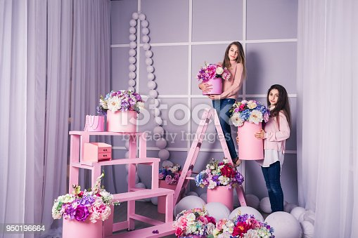 istock Two beautiful girls in jeans and pink sweater in studio with decor of flowers in baskets. 950196664