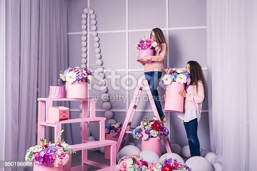 961500822 istock photo Two beautiful girls in jeans and pink sweater in studio with decor of flowers in baskets. 950196668