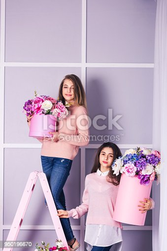 961500822 istock photo Two beautiful girls in jeans and pink sweater in studio with decor of flowers in baskets. 950196670