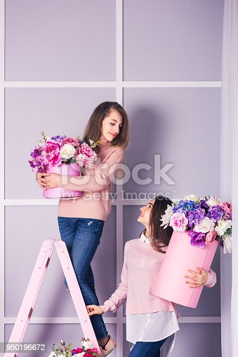 961500822 istock photo Two beautiful girls in jeans and pink sweater in studio with decor of flowers in baskets. 950196672