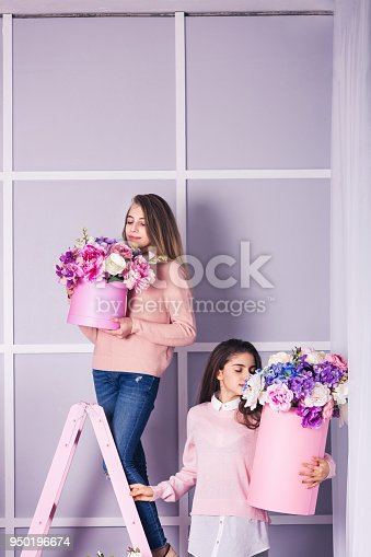 961500822 istock photo Two beautiful girls in jeans and pink sweater in studio with decor of flowers in baskets. 950196674