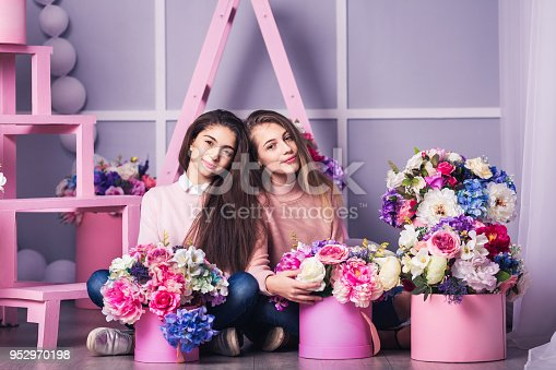 961500822 istock photo Two beautiful girls in jeans and pink sweater in studio with decor of flowers in baskets. 952970198