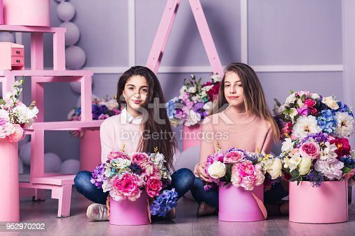 961500822 istock photo Two beautiful girls in jeans and pink sweater in studio with decor of flowers in baskets. 952970202