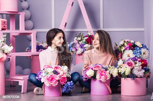 961500822 istock photo Two beautiful girls in jeans and pink sweater in studio with decor of flowers in baskets. 952970206