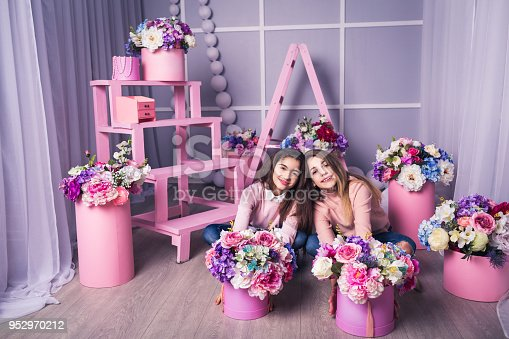 961500822 istock photo Two beautiful girls in jeans and pink sweater in studio with decor of flowers in baskets. 952970212