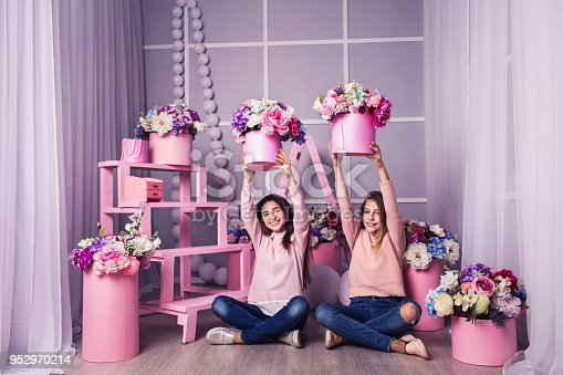 istock Two beautiful girls in jeans and pink sweater in studio with decor of flowers in baskets. 952970214