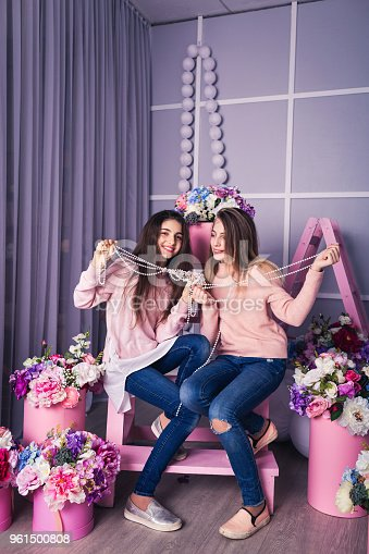 961500822 istock photo Two beautiful girls in jeans and pink sweaters are holding beads in studio with decor of flowers in baskets. 961500808