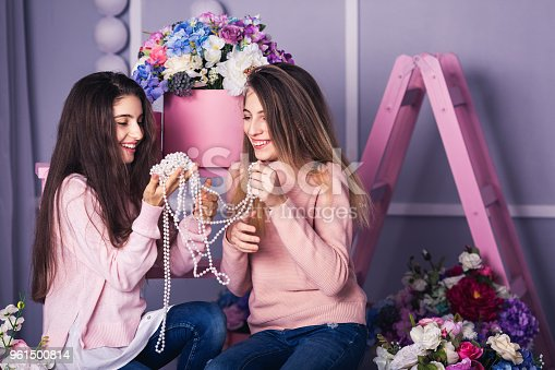 istock Two beautiful girls in jeans and pink sweaters are holding beads in studio with decor of flowers in baskets. 961500814