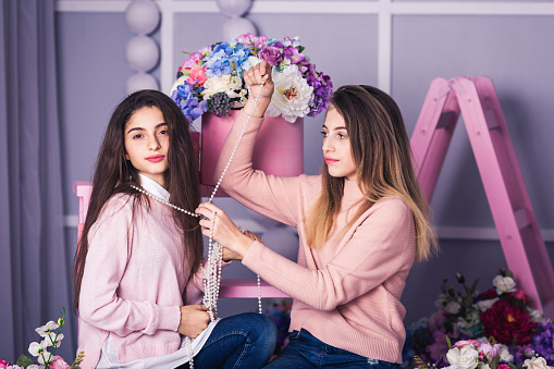 istock Two beautiful girls in jeans and pink sweaters are holding beads in studio with decor of flowers in baskets. 961500822