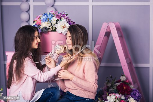 961500822 istock photo Two beautiful girls in jeans and pink sweaters are holding beads in studio with decor of flowers in baskets. 963347496
