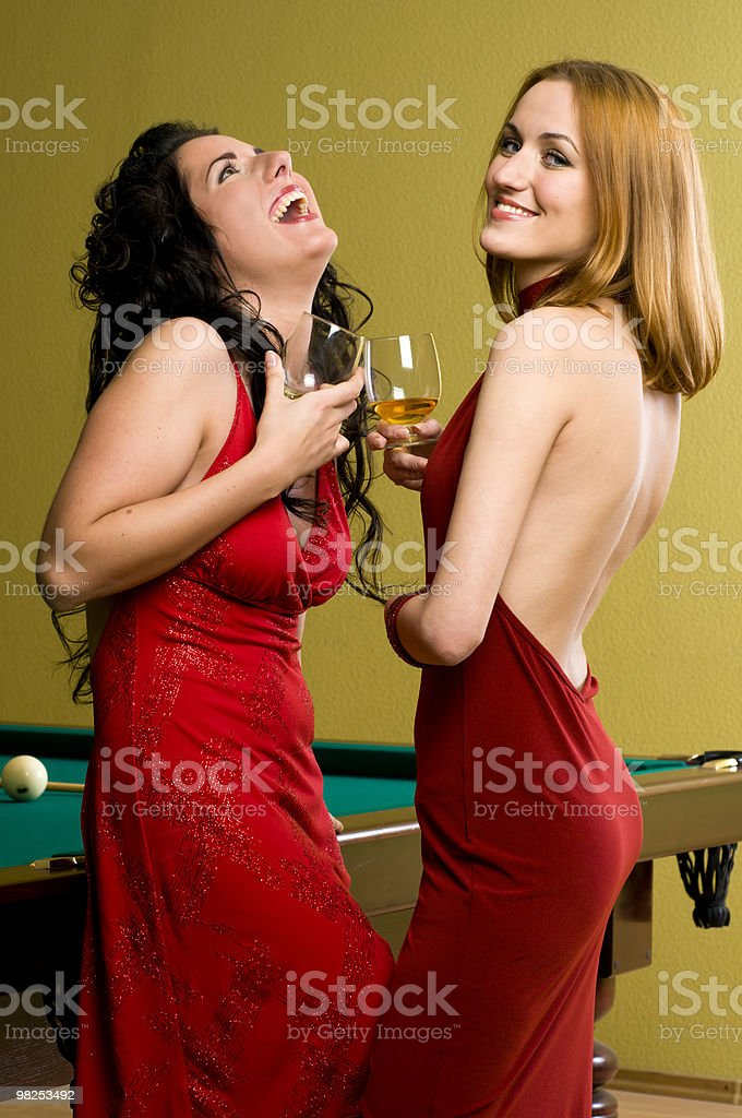 Two beautiful girls in red with cognac royalty-free stock photo