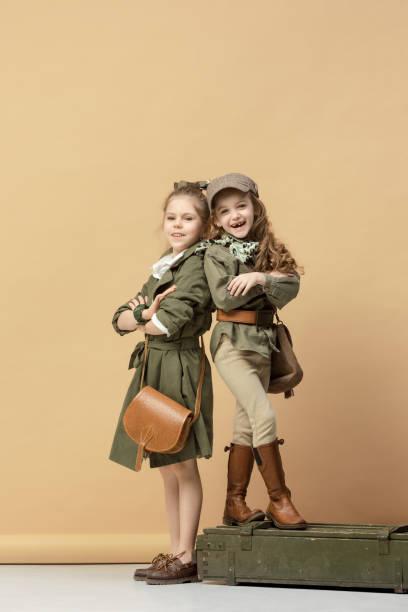 zwei schöne mädchen auf einem pastellfarbenen hintergrund - kinderhandtaschen stock-fotos und bilder