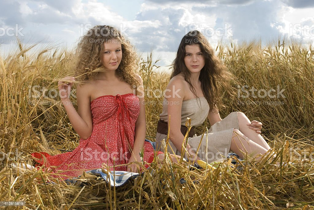 Two beautiful girls on picnic in wheat field royalty-free stock photo