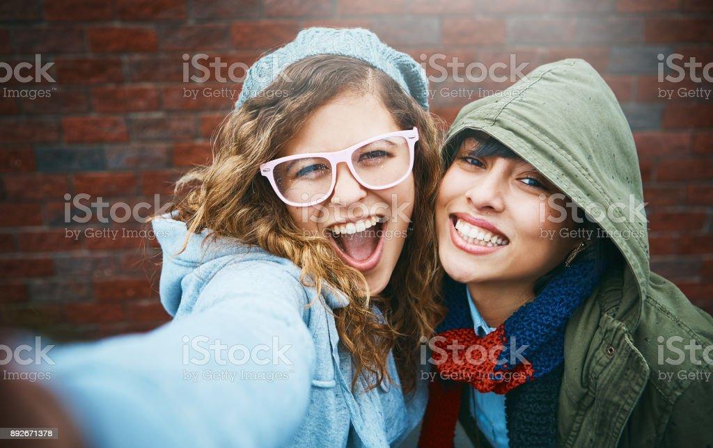 Two beautiful girls take playful smiling selfie outdoors stock photo