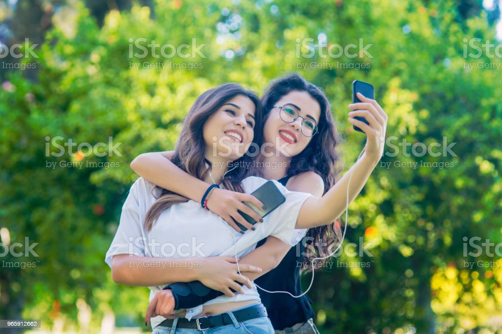 Two beautiful girls take playful smiling selfie outdoors - Royalty-free Adult Stock Photo