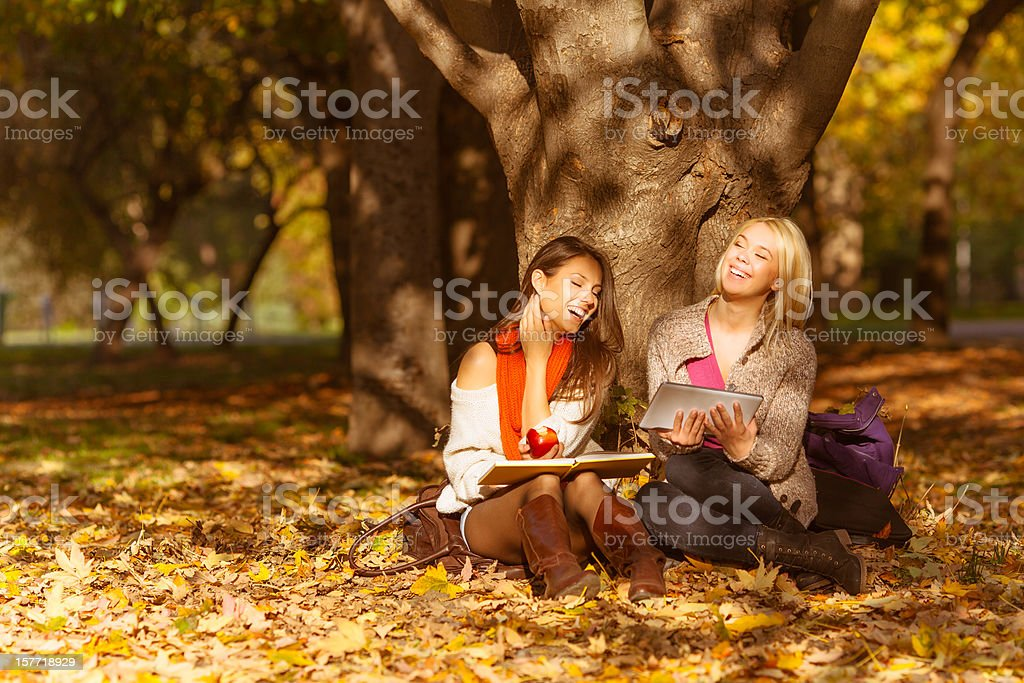 Two beautiful girls using a tablet pc outdoors royalty-free stock photo