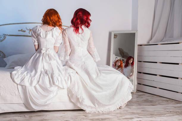 zwei schöne mädchen mit roten haaren in einem schönen weißen viktorianischen brautkleider. weiblichen stil. das fragile mädchen. dünne taille. zwei frauen sitzen im schlafzimmer auf einem weißen bett - festliche kleider kindermode stock-fotos und bilder