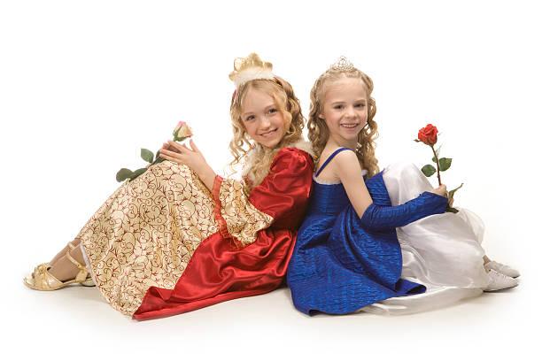 zwei schöne glückliche kleine prinzessinnen sitzen auf boden mit rosen. - prinzessinnenschuhe stock-fotos und bilder