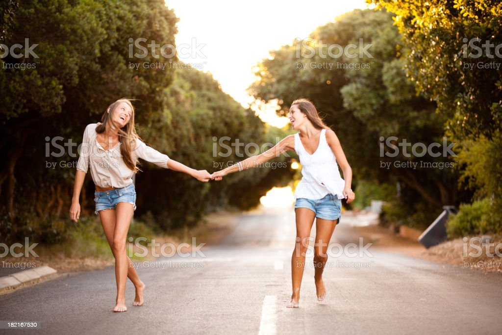 Two beautiful healthy young women skipping down the road together stock photo