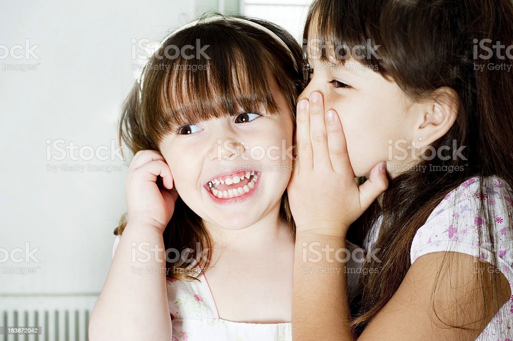 Two beautiful  little girls gossip. royalty-free stock photo