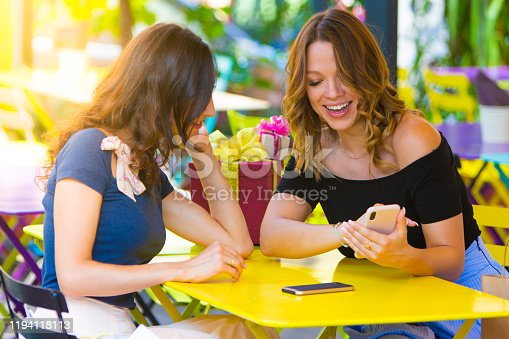 Two beautiful smiling women (best friends) sitting in summer cafe, chatting & looking smartphone together with present boxes behind them. Female friendship, girlfriends, holidays celebrating concept