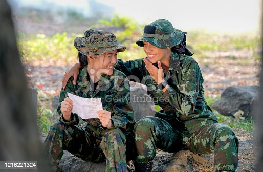 istock Two beautiful soldier women look happy and enjoy with reading letters from someone 1216221324