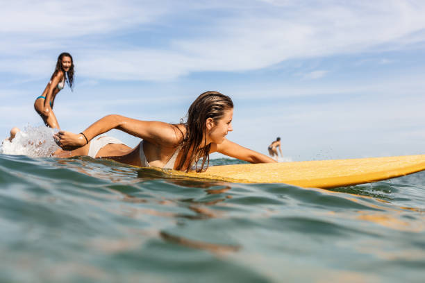 two beautiful sporty girls surfing in the ocean. - surf foto e immagini stock