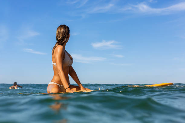 Two beautiful sporty girls surfing in the ocean. stock photo