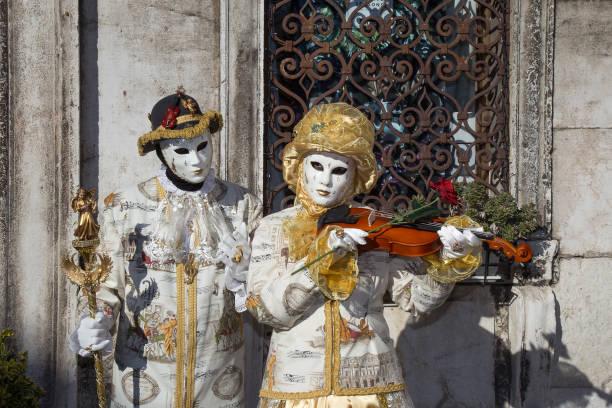 zwei schöne venezianische masken mit violine, liebe, rose, herz, san zaccaria platz, venedig, italien - rosa camo party stock-fotos und bilder