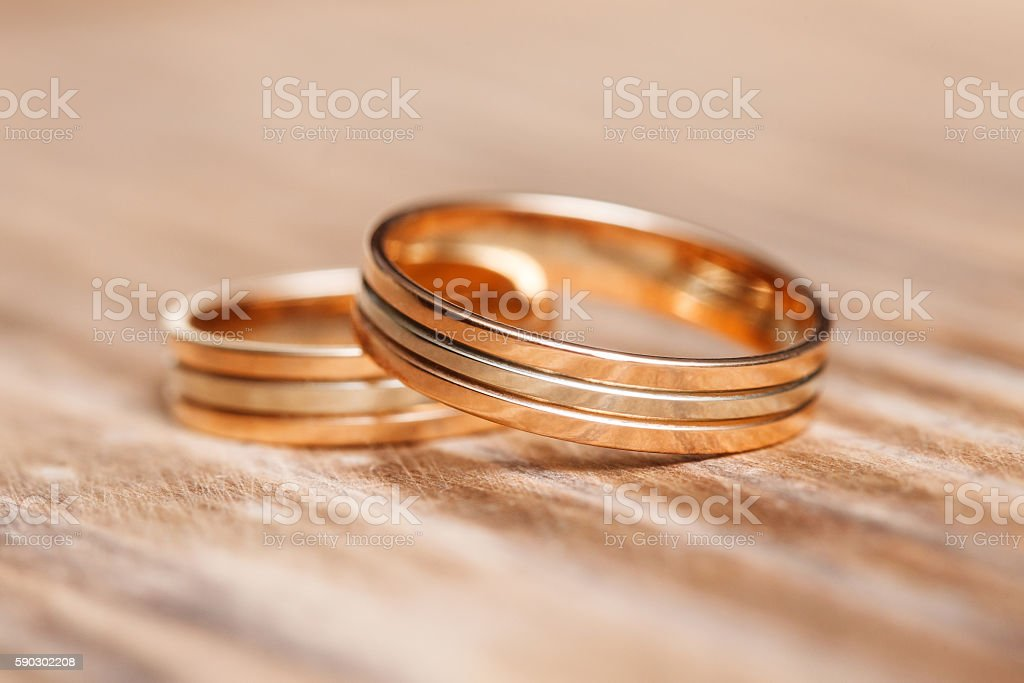 Two beautiful wedding rings on wooden background, close up royaltyfri bildbanksbilder