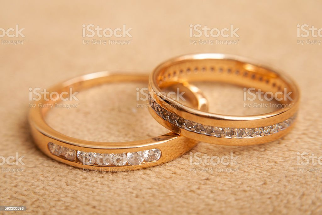 Two beautiful wedding rings with brilliants close up. Marriage concept Стоковые фото Стоковая фотография